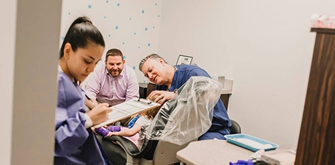 Dentist and team member treating young patient with smiling parent in room