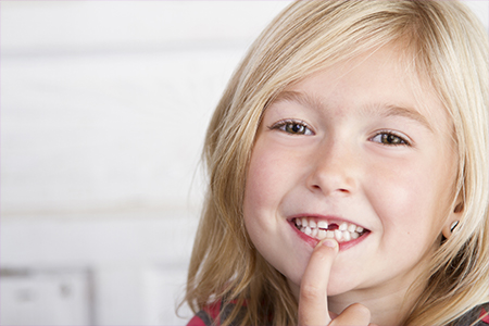 Little girl pointing to last baby tooth