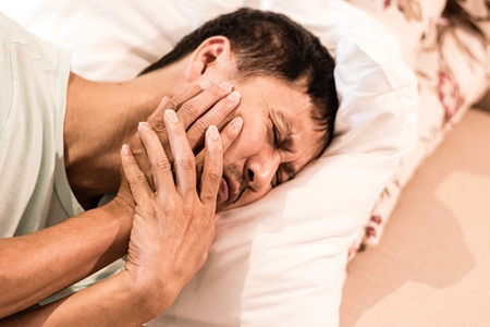 person laying in bed with a toothache