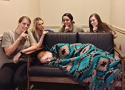 Team member with one team member sleeping on couch