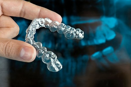close up of person holding aligner in front of dental x-rays