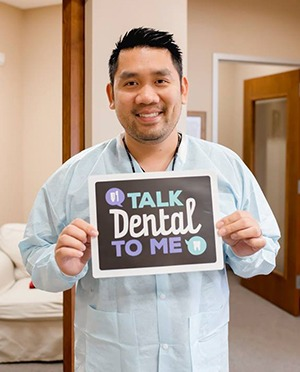 Dr. Lam holding a Talk Dental to Me sign