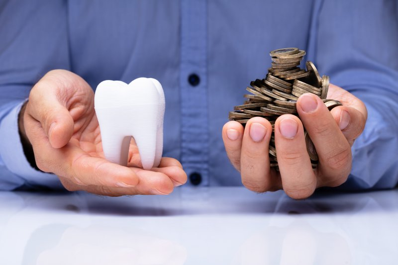 man holding tooth and coins