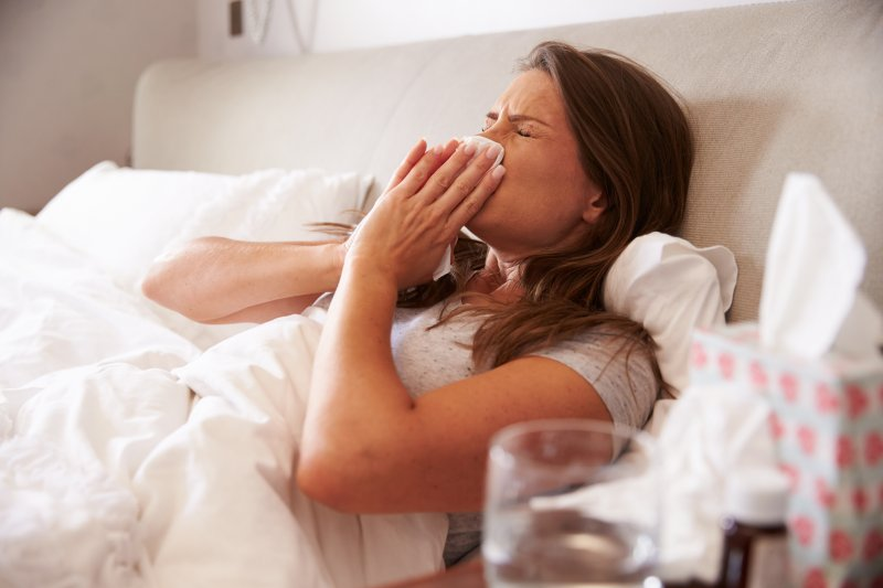 Woman suffering from a cold in bed